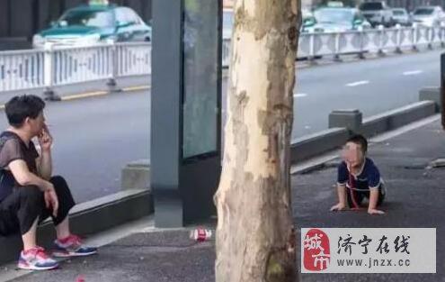 大妈坐看3岁孙子学狗爬用嘴叼玩具蛇