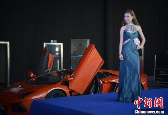 9月23日,世界旅游小姐在跑车旁身着华丽的礼服走秀,争当豪车大使
