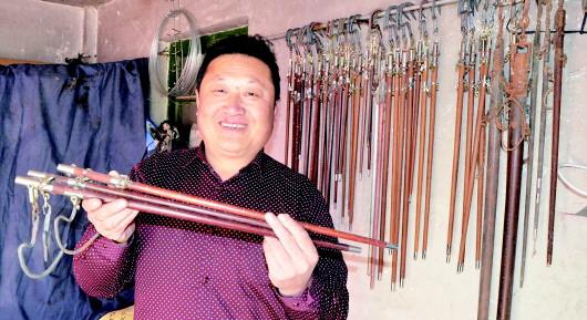 孙连勇和他手工制作的杆秤。 文/图 半岛记者 李春燕 随着电子秤、弹簧秤等计量工具的广泛应用,曾经红火一时的手工杆秤逐渐走出了人们的视野。但是在即墨市金口镇,仍然有这样一位手工制秤人,他默默坚守着祖辈流传下来的老手艺,30年间做了4万余杆秤,他就是46岁的老手艺人孙连勇,在当地也被称为最后一位制秤手艺人。 一支杆秤至少40多道工序 刮杆、量尺寸打孔、不锈钢包头、安装秤刀、校秤、画斤两标线、钻星眼这是最基本的步骤,细算的话,至少需要40多道工序。11月9日,记者在即墨市金口镇庙东一村见到了在当地