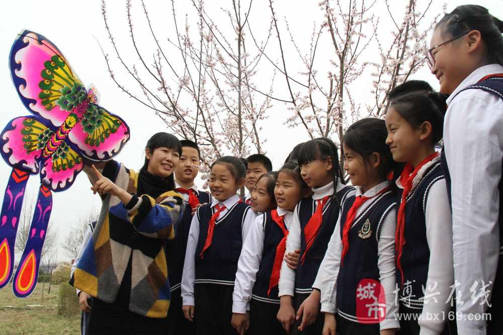 三小学教师王敏向五年级(五)班的小学生展示风筝,一起感受美好的春天