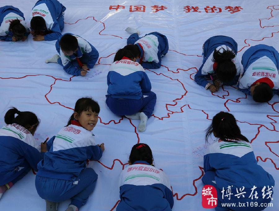 """在博兴县实验小学,小学生正在一幅中国版图上共同书写自己的""""中国梦""""."""