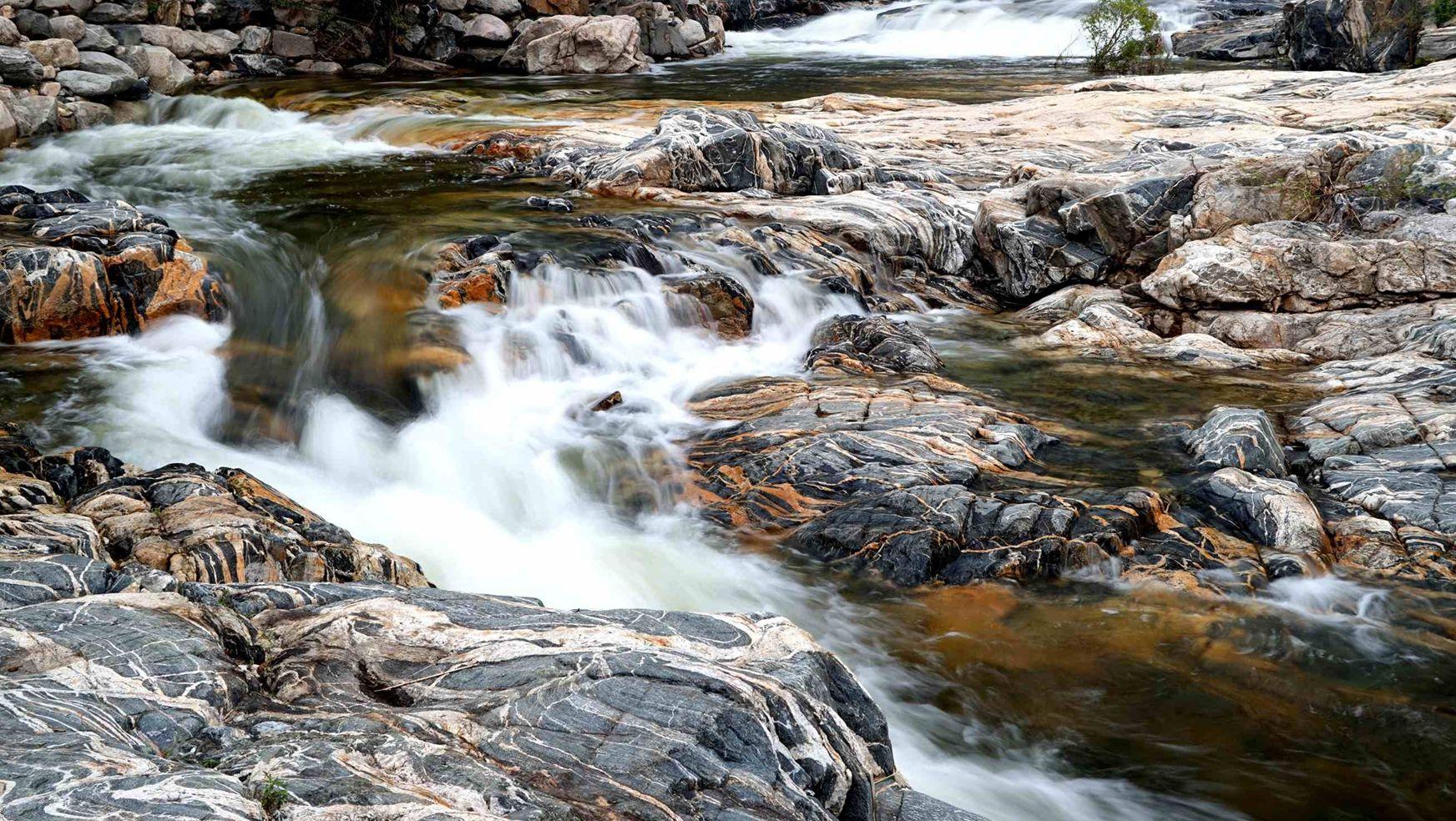 泰山彩石溪位于泰山西麓的桃花峪景区内,长约2公里,溪中流水之下忽如彩石铺就,溪底一条条石纹五彩纷呈,阳光照耀下,分外生动,这就是著名的彩石溪。 弯弯曲曲的溪水像是被彩石染上了色,也像是一条五彩的飘带,在此流淌得格外精神。动人的彩石常引得游人驻足,如果你细心,就可看见水中的赤鳞鱼。 水在石上流,石在水下走。 彩石溪,画入水中秀,水在画上流。沿溪可观赏色彩斑斓的带状彩石。十八亿年五世同堂的地质奇观。十里山涧,彩石平铺溪底。波光潋滟,奇特地质地貌,犹如泼墨大写意。 沿溪而上漫步于乱石铺阶的步游路可欣赏那四时不